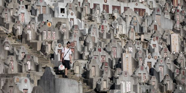 A man walks past tombstones at a cemetery ahead of the Ching Ming Festival, or grave-sweeping day, in...