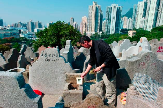 A man burns paper offerings at the grave of a relative during the Chung Yeung grave sweeping festival at a cemetery in Hong Kong.