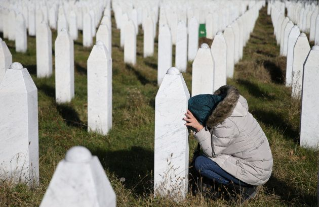 A woman sits by the grave of a family member near Srebrenica, Bosnia and Herzegovina, after the court...