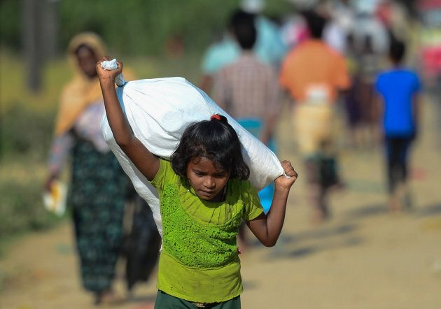 A Rohingya Muslim refugee child carries relief aid through Balukhali refugee camp in the Ukhia district of Bangladesh.