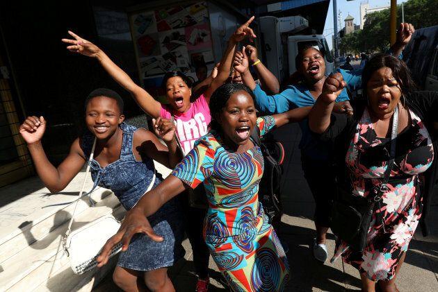Zimbabweans celebrate in the morning sun after President Robert Mugabe resigned in Harare, Zimbabwe.