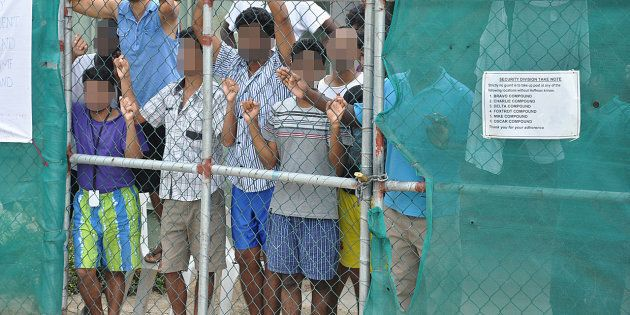 Asylum-seekers look through a fence at the Manus Island detention centre in Papua New Guinea March 21,