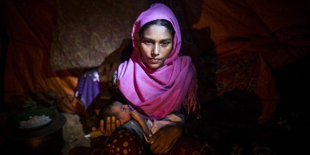 October 11, 2017: Nur Kayida, 20, is seen with her two-day-old baby with no given name at a makeshift camp in Cox's Bazar, Bangladesh.