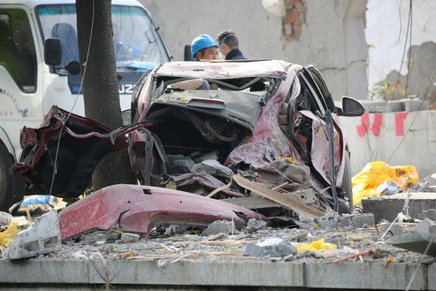 A damaged car is seen at the site of a blast in