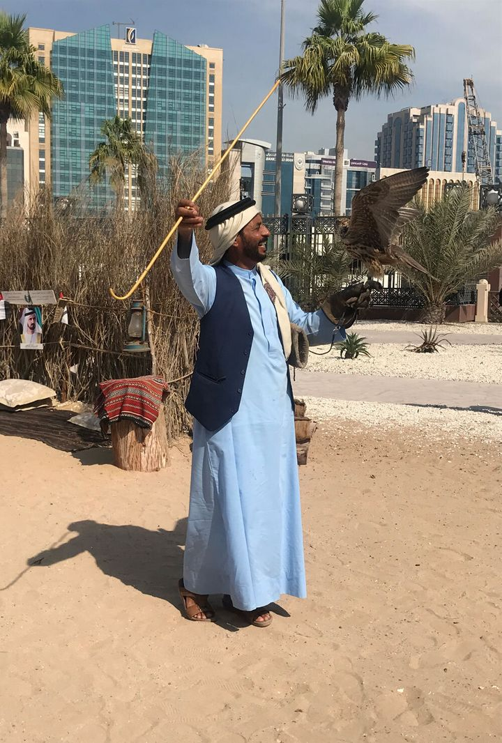 A man poses with his falcon in the historical Al Fahidi District.