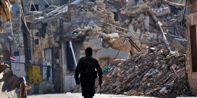 A Syrian pro-government fighter walks past damaged buildings in the Bab al-Nasr district of Aleppo's...