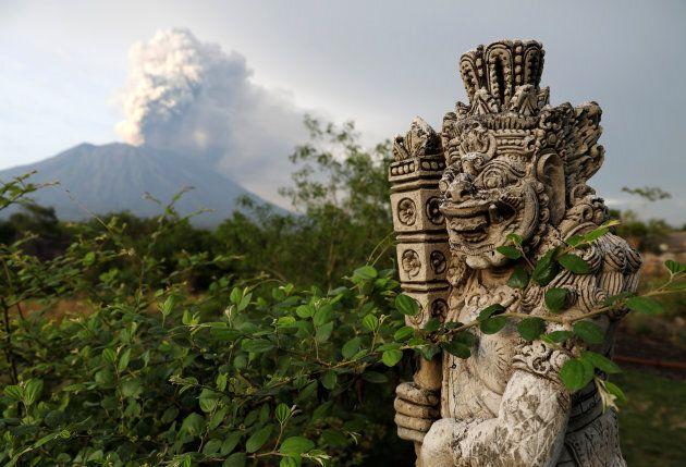 A statue on a bridge is seen as Mount Agung volcano erupts in the background near Kubu, Karangasem Regency,
