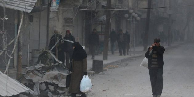 People carry their belongings as they flee deeper into the remaining rebel-held areas of