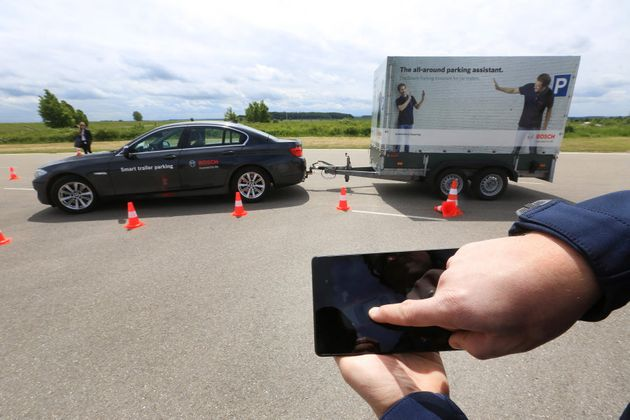 A Bayerische Motoren Werke AG (BMW) automobile is parked via a mobile device remote control during a...