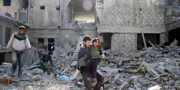 A man carries an injured boy as he walks on rubble of damaged buildings in the rebel held besieged town...