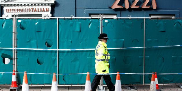 A police officer stands on duty outside a restaurant which has been secured as part of the investigation...