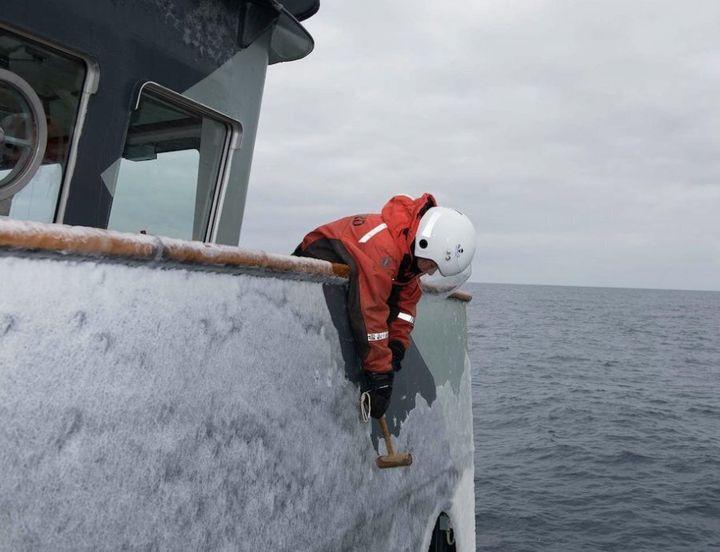 Elissa Sursara removing ice from the bridge wing of the MV Sam Simon.