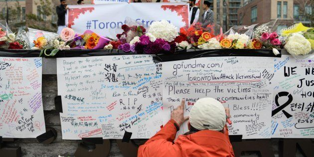 A man writes a message at a memorial on Yonge Street the day after a suspect drove a rented van down...