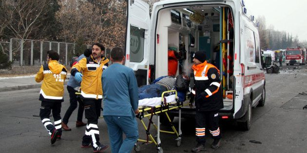 TURKEY OUTThis picture obtained from the Ihlas News Agency shows a police officer and people walking next to the wreck of public bus following an explosion on December 17, 2016 in Kayseri, central Turkey.Several people were wounded on December 17 in a car bombing close to the public bus in the central Turkish city of Kayseri, television reports said. The Dogan news agency said that the blast took place opposite the Erciyes University in the city. NTV television said there could be fatalities as a result of the blast. The state-run Anadolu news agency said that the bus was owned by the municipal transport authorities in Kayersi but was transporting Turkish soldiers who had taken permission to go to a local market for the day. / AFP / IHLAS NEWS AGENCY / IHLAS NEWS AGENCY / Turkey OUT        (Photo credit should read IHLAS NEWS AGENCY/AFP/Getty Images)