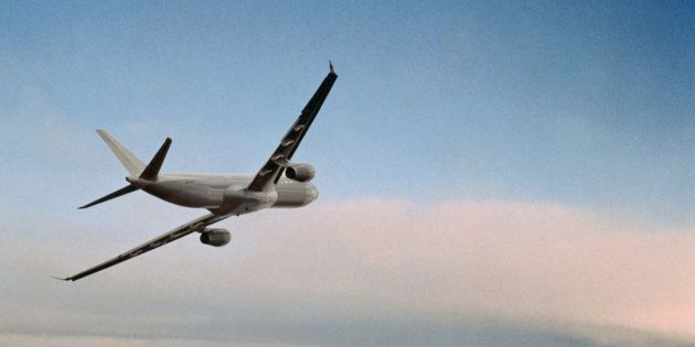 Jet airplane flying above clouds, low angle view