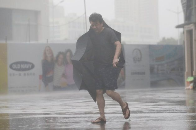 A man holding an umbrella walks in rain as Typhoon Mangkhut approaches, in Shenzhen,