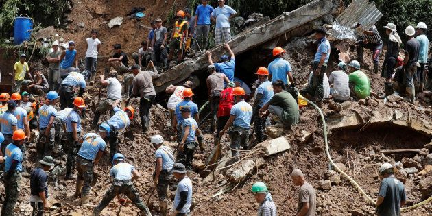 Rescuers search for people trapped in a landslide, after super typhoon Mangkhut hit the country, at a...