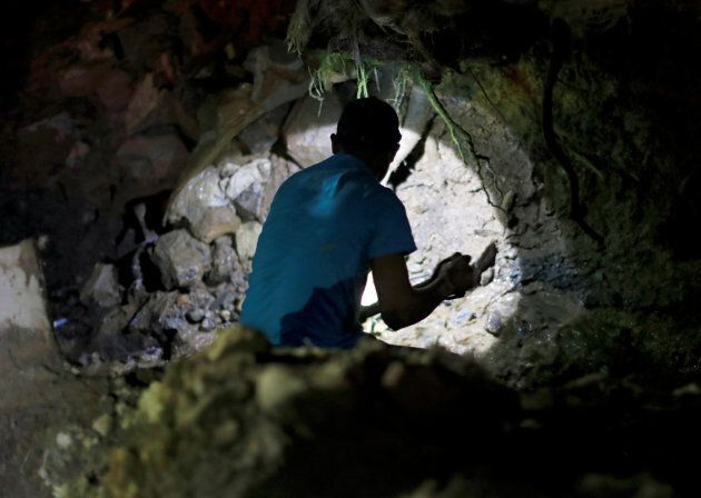 A miner takes part during a search for fellow miners missing after a landslide caused by Typhoon Mangkhut...