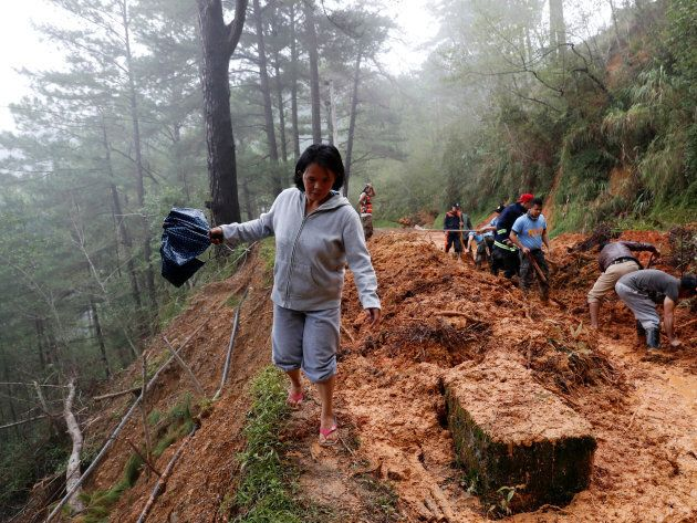A resident walks on the side of a road as police officers and fire marshals clear debris and fallen trees caused by a landslide at the height of Typhoon Mangkhut.
