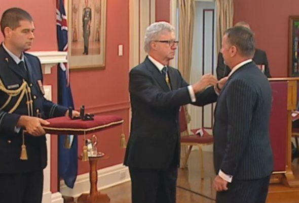Queensland Governor Paul de Jersey presents a bravery award to John Tyson, who received it on behalf...