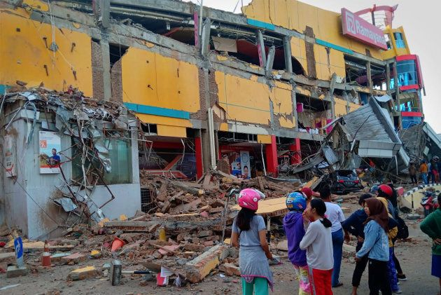 Residents stand in front of a damaged shopping mall after an earthquake hit Palu, Sulawesi Island, Indonesia...