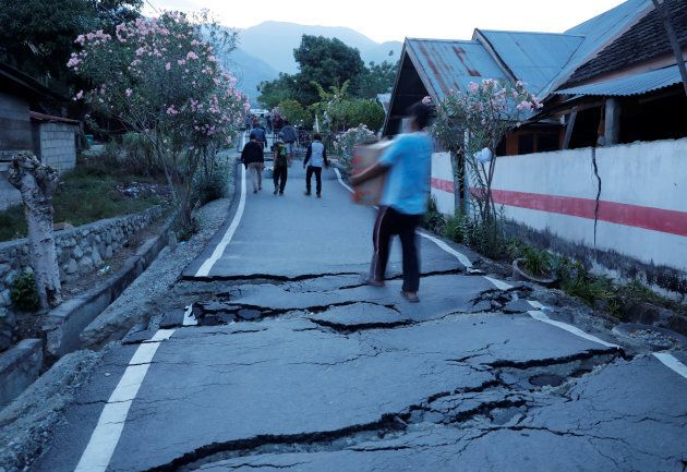 Residents walk on cracked tarmac as they carry their belongings after an earthquake hit at Balaroa sub-district...