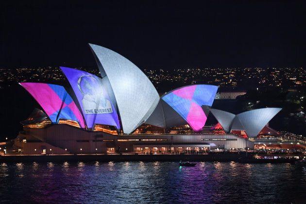 Protestors use torches and other lights to shine onto the sails of the Opera House during a promotional light show.