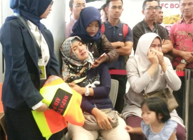 Relatives of passengers of Lion Air flight JT610 that crashed into the sea, cry at Depati Amir airport...