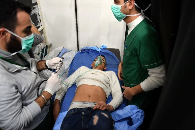 A man breathes through an oxygen mask inside a hospital after what the Syrian state media said was a...