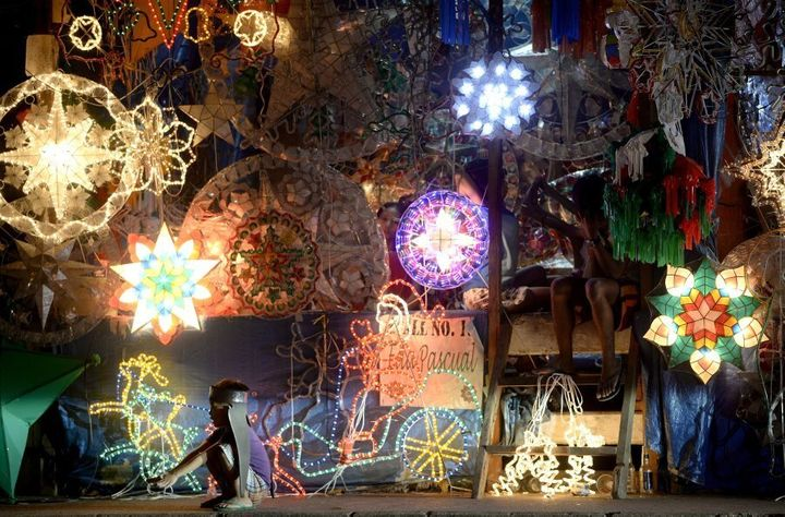 A boy crouches beside Christmas lanterns in the Philippines.