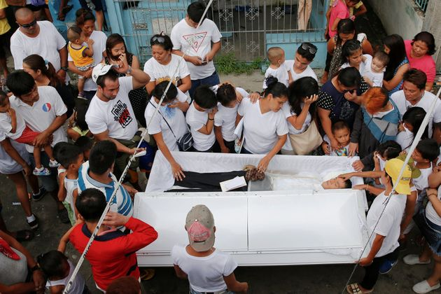 Relatives and friends gather around the coffin of Benjamin C. Visda Jr, who was killed during a police...