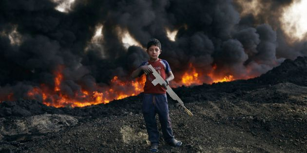Zaer Ibrahim*, 8 plays by the burning oil fields in Qayyarah. *Name changed to protect
