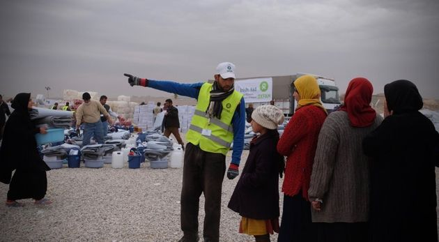 Oxfam staff organise the distribution of supplies to IDPs in Hassansham Camp, about 50km East of