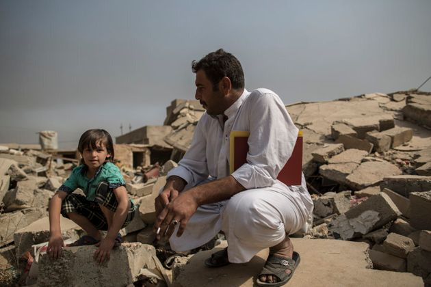 Mokhtar (village head) Nisr Amr, 35, sits with his son in the ruins of his father's house in the village...