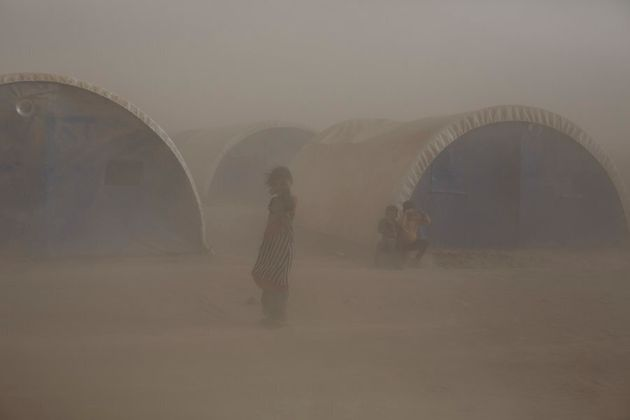 A dust storm engulfs a camp for displaced people in the village of Tinah some 70km south of Mosul, Iraq,...