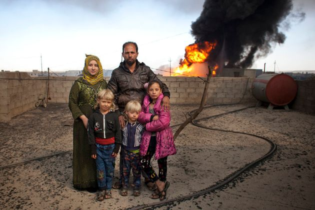 Ibrahim Mohammed with wife Soma Selwan stand on the roof of their home with their children Luma 11, Aws...