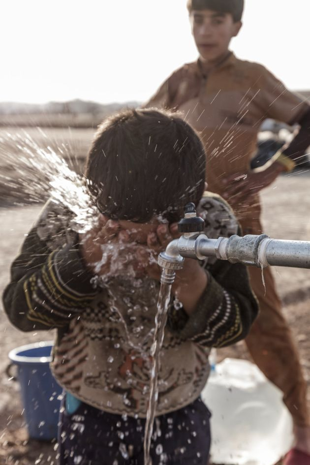 Children wash their faces in Hassansham camp around 50km east of Mosul. Hundreds of families have been...