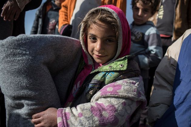 *Rasha, 7, holds a blanket given to her family by Oxfam as part of a distribution of blankets, nappies,...