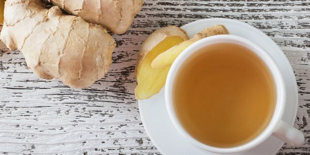 Ginger tea in a white cup on wooden