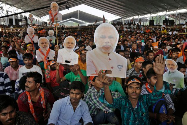 Supporters of India's ruling party Bharatiya Janata Party (BJP) hold cut out busts of Indian Prime Minister...