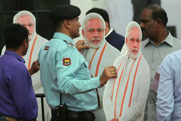 A private security guard stands holding cut-outs of Indian Prime Minister Narendra Modi, to be placed...