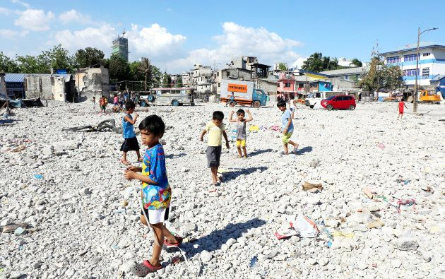 Children play where a fire recently destroyed a block of makeshift homes in a low-income area of