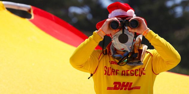 A surf lifesaver looks through binoculars while wearing a Christmas hat on Christmas Day at Sydney's...