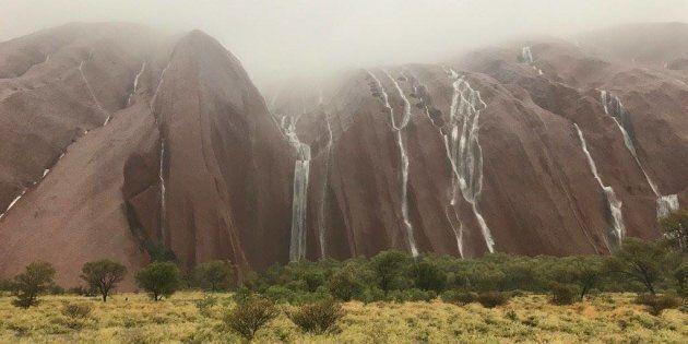 Rain cascades down Uluru.