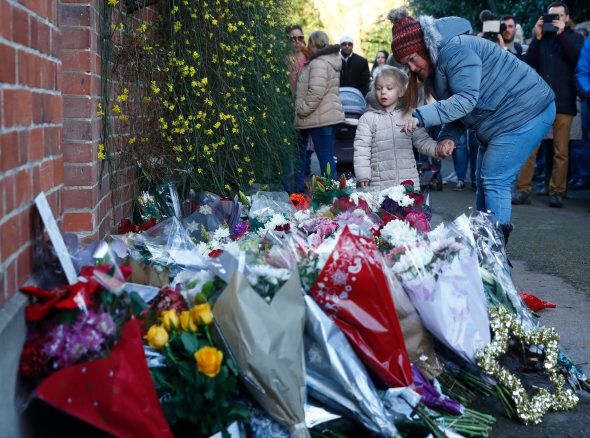 A woman and child look at tributes outside the house of singer George Michael, where he died on Christmas...