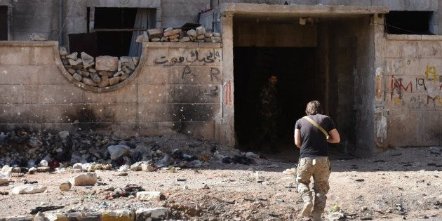 A Syrian pro-government soldier runs for cover in the '1070' apartment block area, south of al-Hamdaniyah, in eastern Aleppo