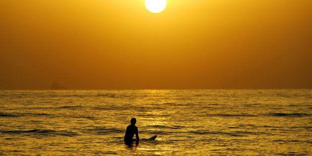 A surfer enjoys a cool surf at sunrise at Sydney's Manly