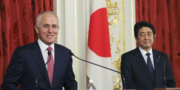 Australian Prime Minister Malcolm Turnbull (L) speaks as his Japanese counterpart Shinzo Abe listens...