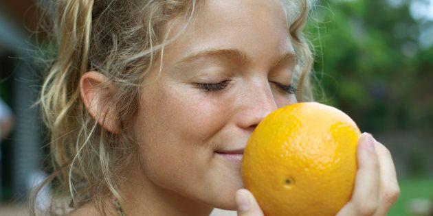 Woman smelling fresh orange