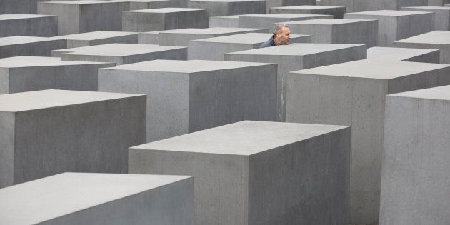 GERMANY, BERLIN - APRIL 04: A visitor between the stelae of the Holocaust Memorial in Berlin. (Photo by Ulrich Baumgarten via Getty Images)